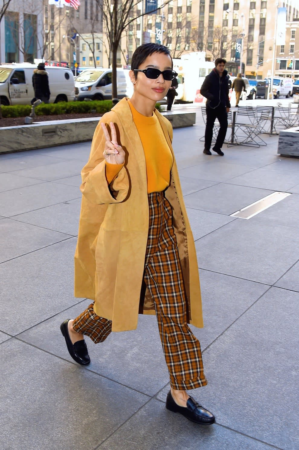 Zoe on a sidewalk in long jacket plaid pants loafers giving peace sign