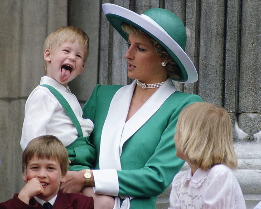 Diana segurando Harry no colo, ele está mostrando a língua para a foto.