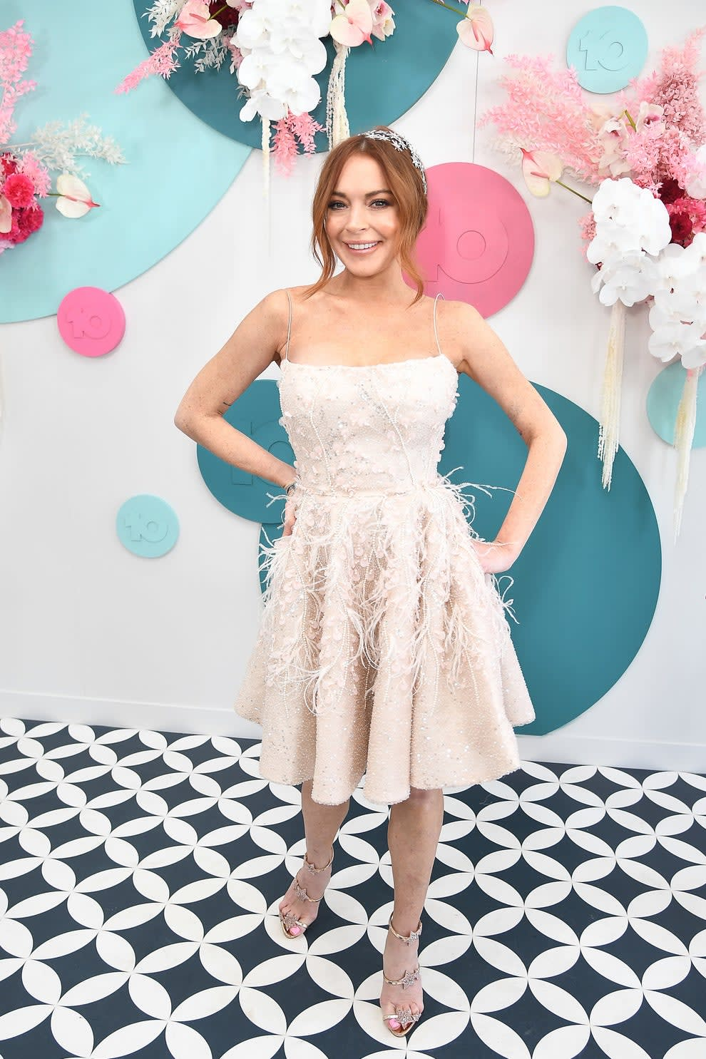 Lindsay wears a knee length dress with feathers and flowers on it. She has her hair pulled back in a headband with stars on it and she also has three stars on each of her shoes.