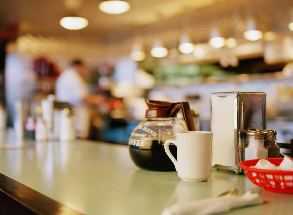 a table in a diner with a pot of coffee and napkins on it