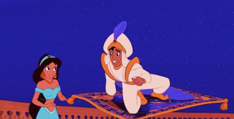 Aladdin, wearing a turban, picks up Princess Jasmine on his magic carpet