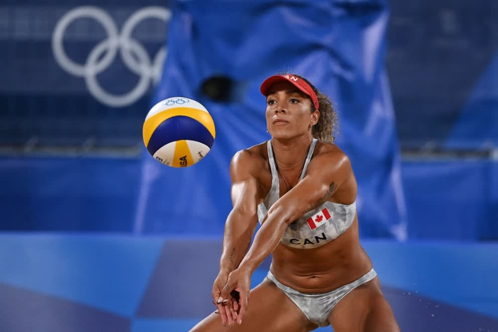 A Canadian beach volleyball player preparing to hit the ball