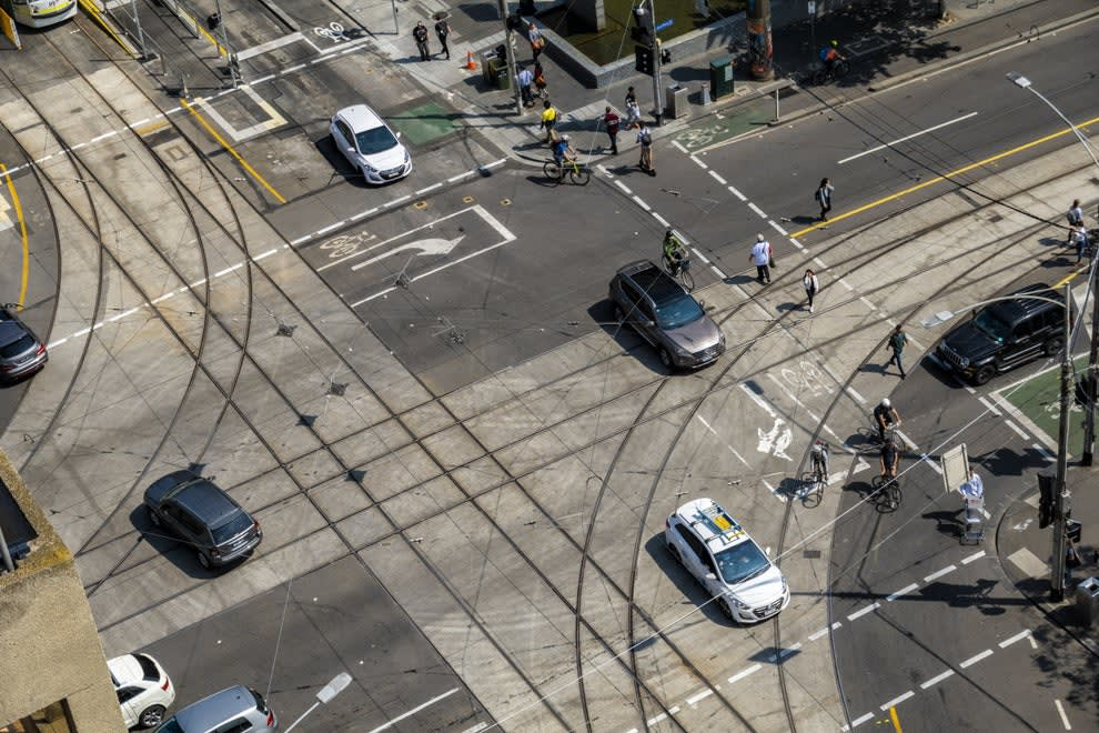 intersection during the day time with cars, bikers, and pedestrians