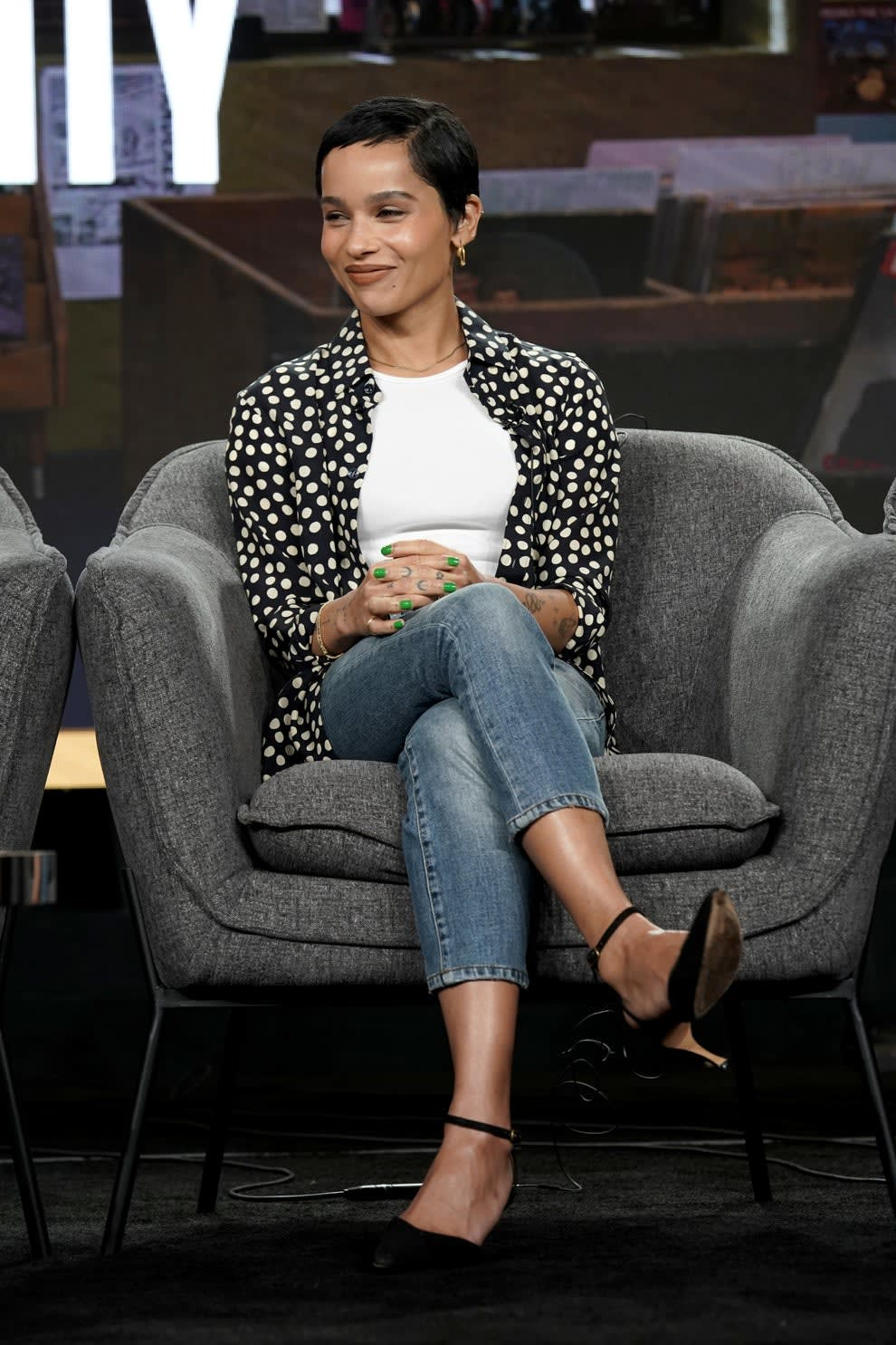 Zoe sitting in a puffy chair in jeans polka dot shirt and high heels