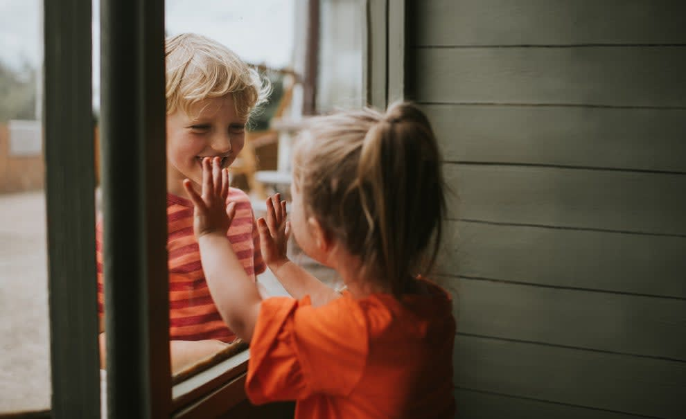 Two toddlers innocently smile at each other through a window