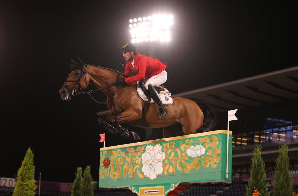 Olympic equestrian on a horse jumping over an obstacle