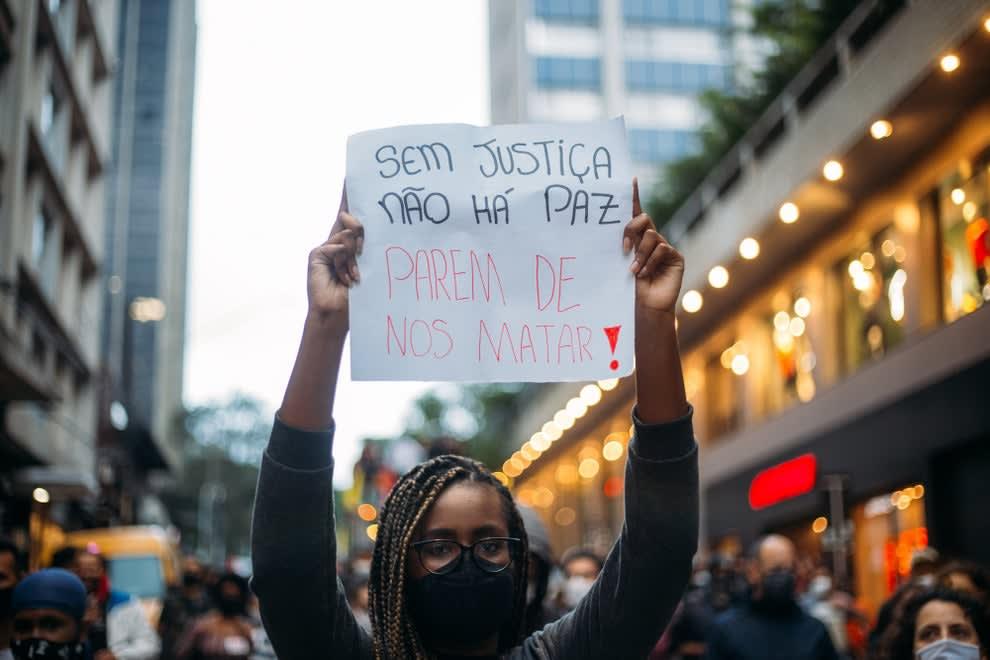 """Mulher negra usando tranças e segurando cartaz onde se lê """"sem justiça não há paz, parem de nos matar"""""""""""