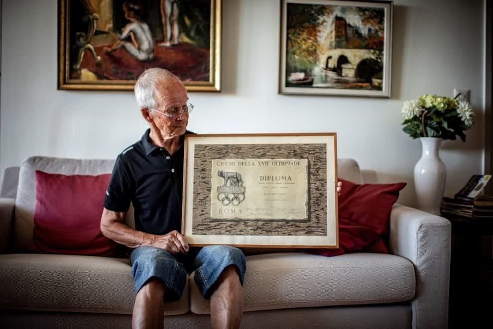 A former Olympian poses with his Olympic diploma