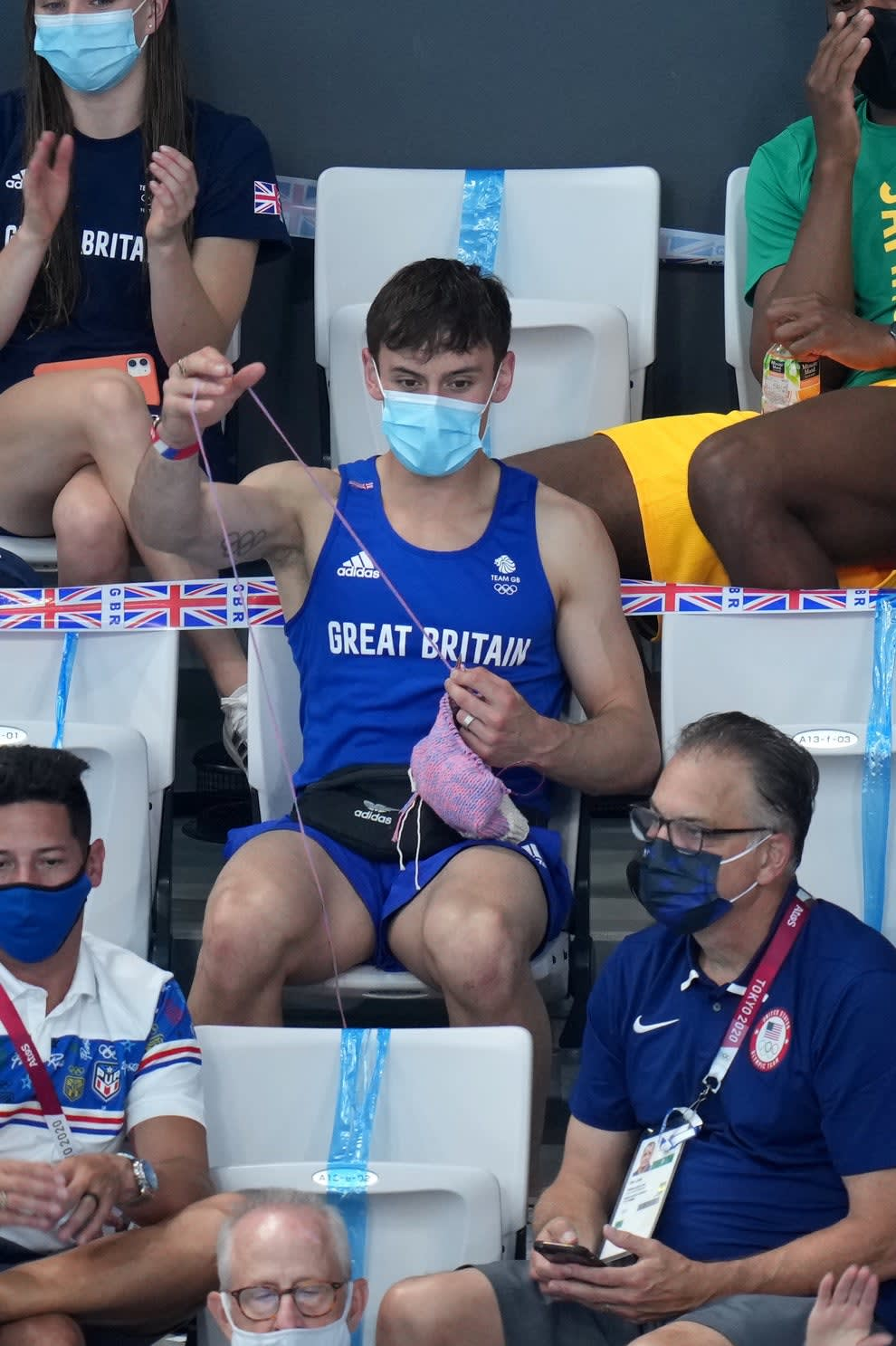 Tom knitting in the stands as he looks at the diving pool