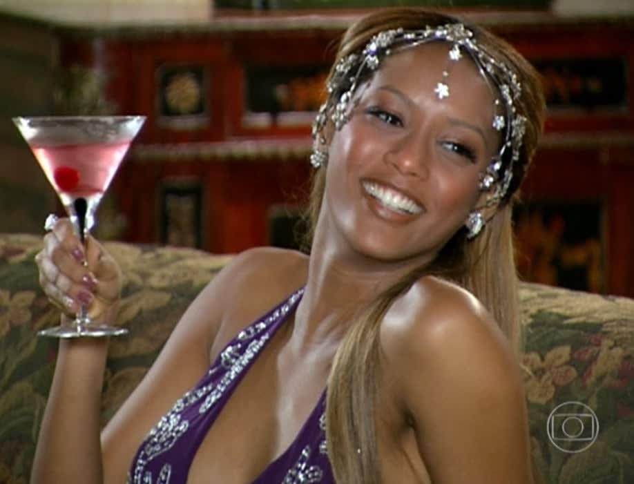 Uma mulher negra com um arranjo de cabeça feito de flores e estrelas brilhantes. Ela está segurando um drink em um copo de martini.