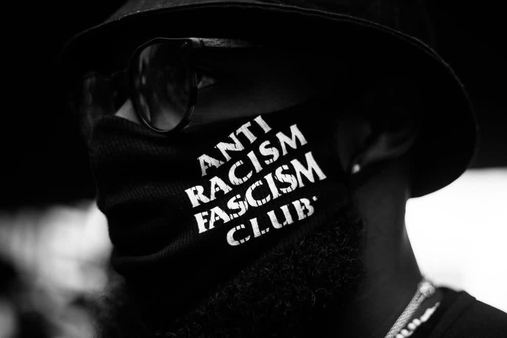 Close de rosto pessoa negra escondido atrás de máscara preta onde se lê em letras brancas ANTI RACISM FASCISM CLUB.