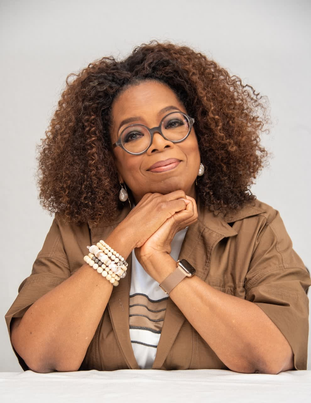 Oprah Winfrey rests her head on her hands while sitting at a table