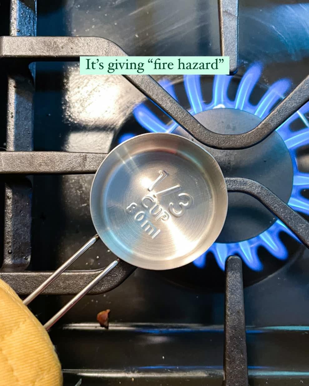 copo de medição de aço inoxidável sobre a chama em um fogão