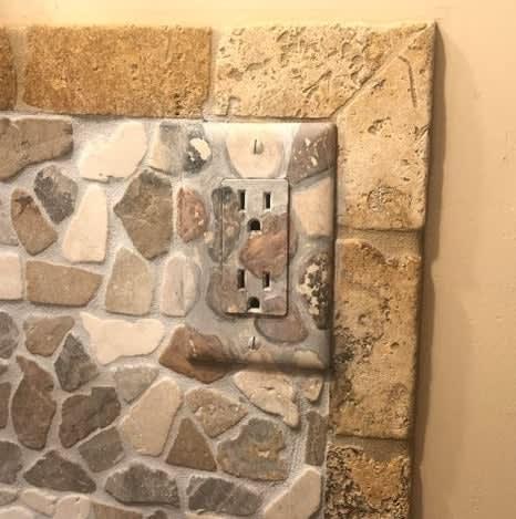 Uma tomada de prede pintada com o desenho das pedras em volta