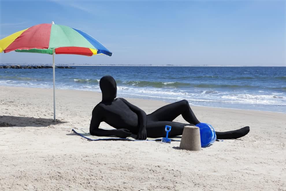 man in morph suit sunbathing on the beach