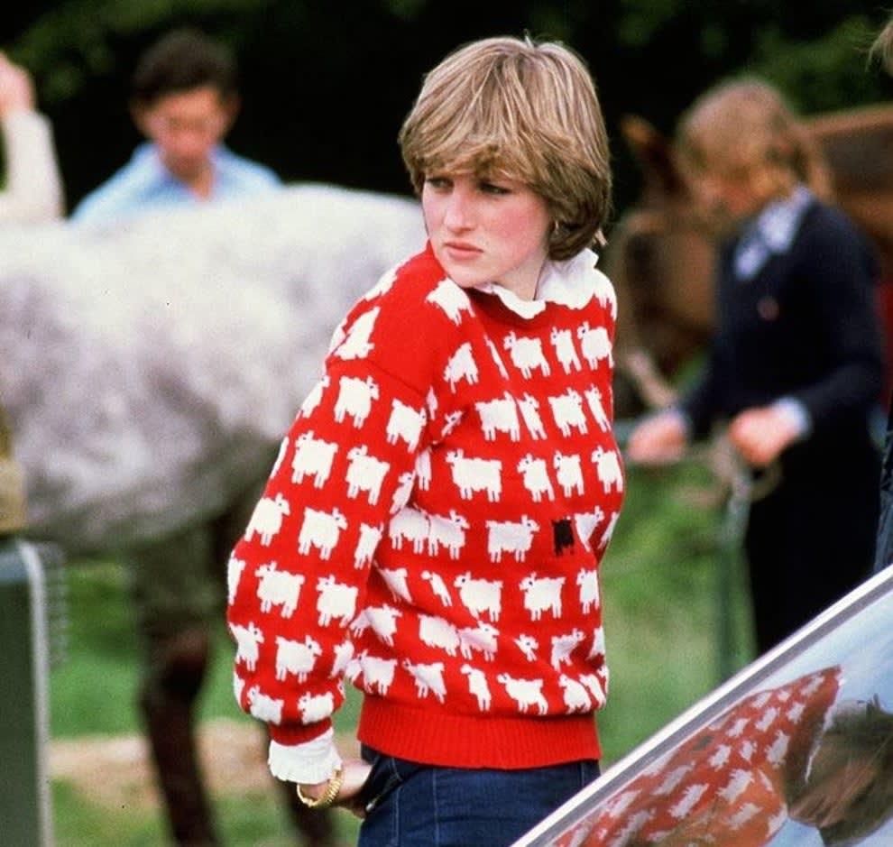 Diana usando um suéter vermelho com ovelhas brancas e pretas estampadas.