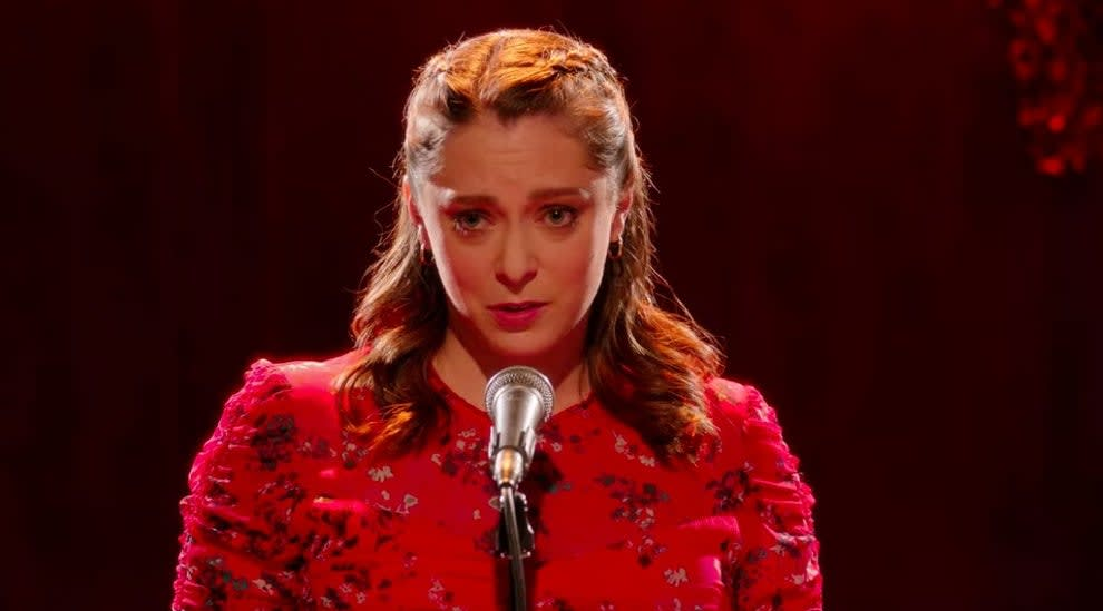 Rebecca stands in front of a microphone looking concerned