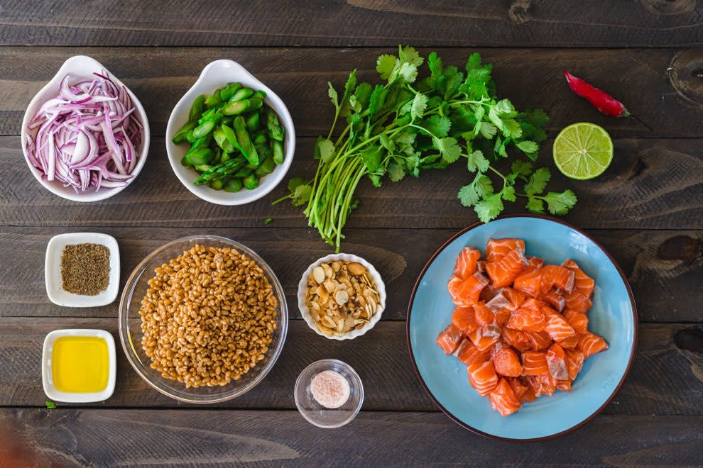 Various ingredients like cubed salmon, grains, onions, herbs, and oil all mise en place.
