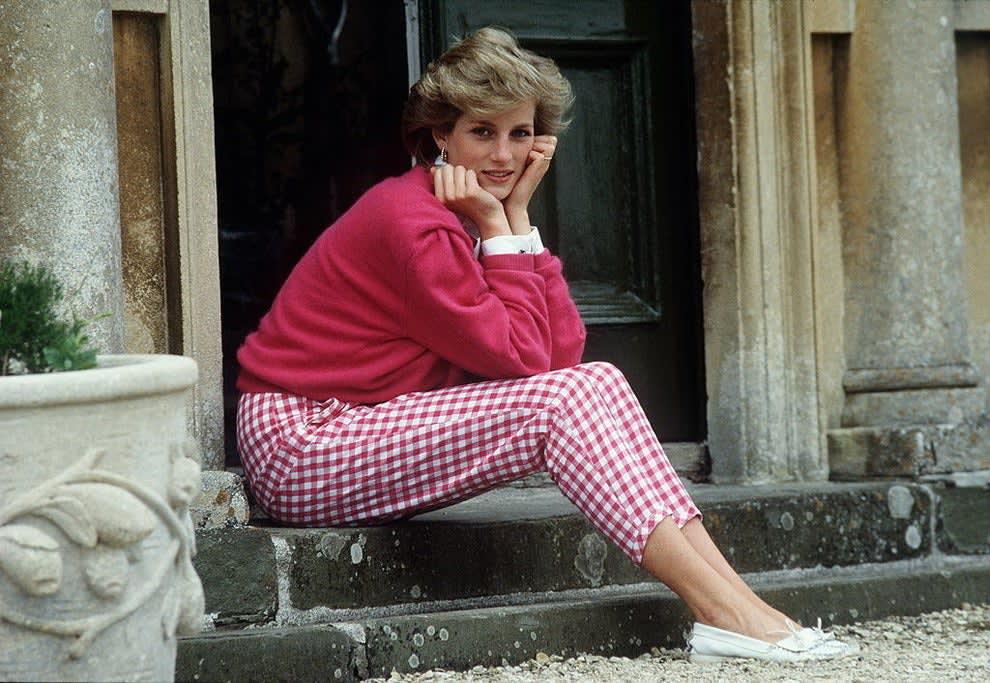 Diana sentada em um degrau, posando com as mãos no queixo.