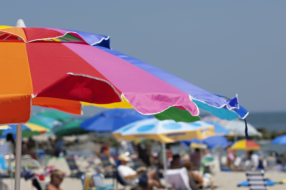a beach umbrella with a blurry, busy beach in the background