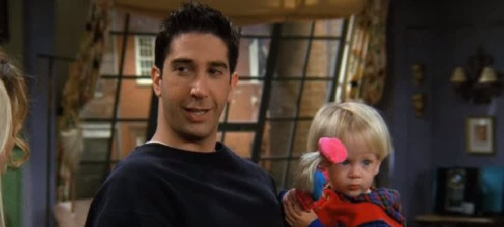Cena de Ross Geller na série. Ele veste uma blusa azul na casa de Mônica e segura seu filho, que por sua vez, está brincando com uma Barbie.