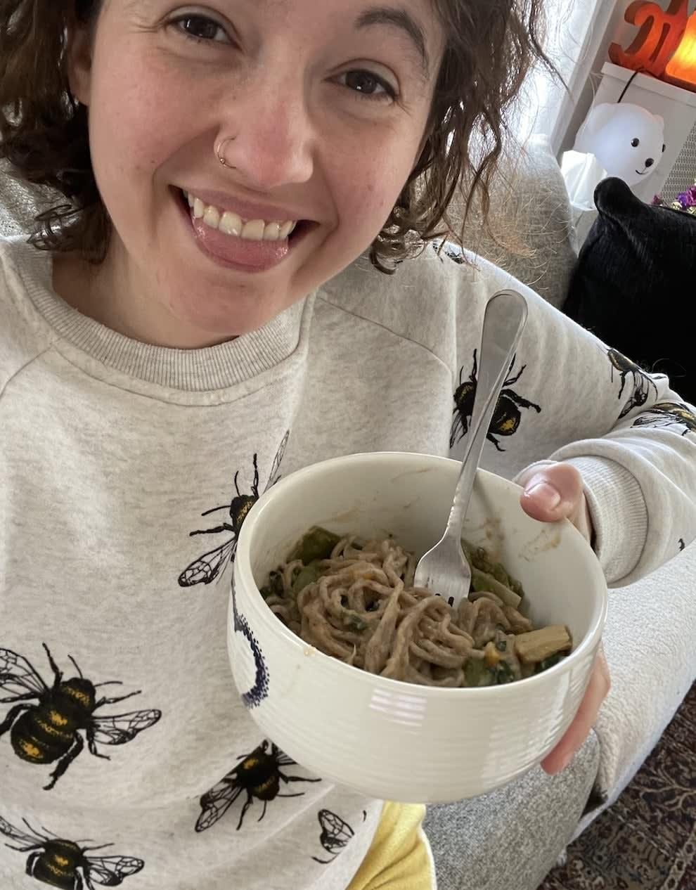 A person holding ginger sesame noodles