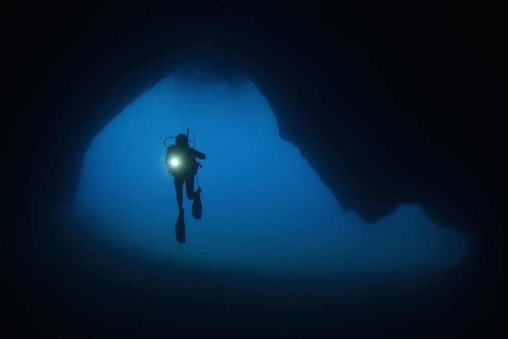 Someone cave diving in a dark underwater cave