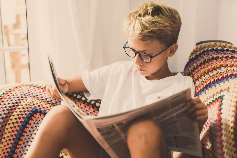 Kid on couch looking at newspaper