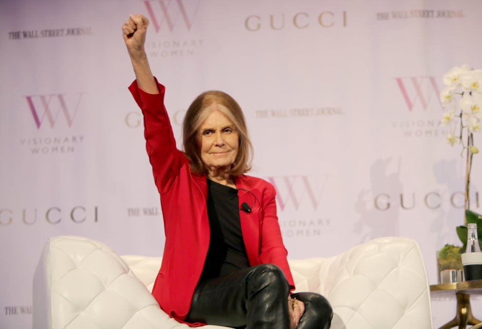 Gloria holding her fist up as she sits during an interview