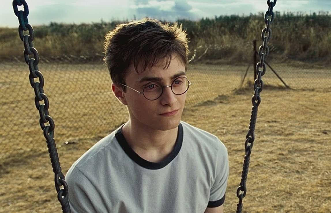 """Daniel Radcliffe sentado em um balanço na cena de """"Harry Potter"""""""