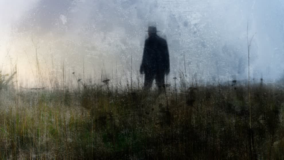 Silhouette of a man with a wide-brimmed hat walking in the tall grass