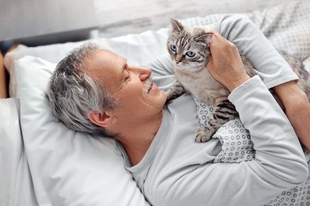 Foto de um homem deitado com um gato no colo