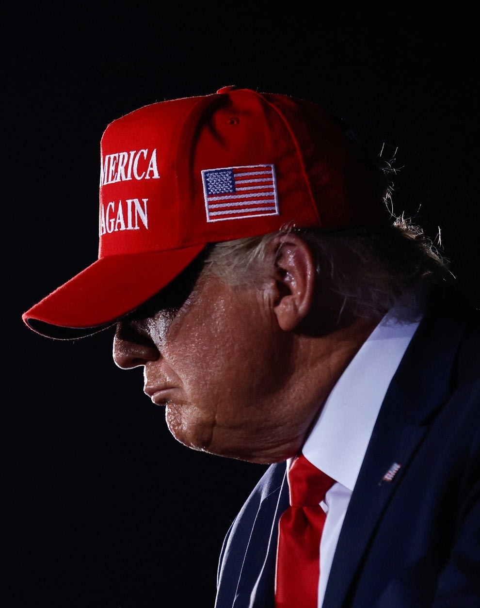 Donald Trump de perfil sobre fundo escuro, usando boné vermelho.