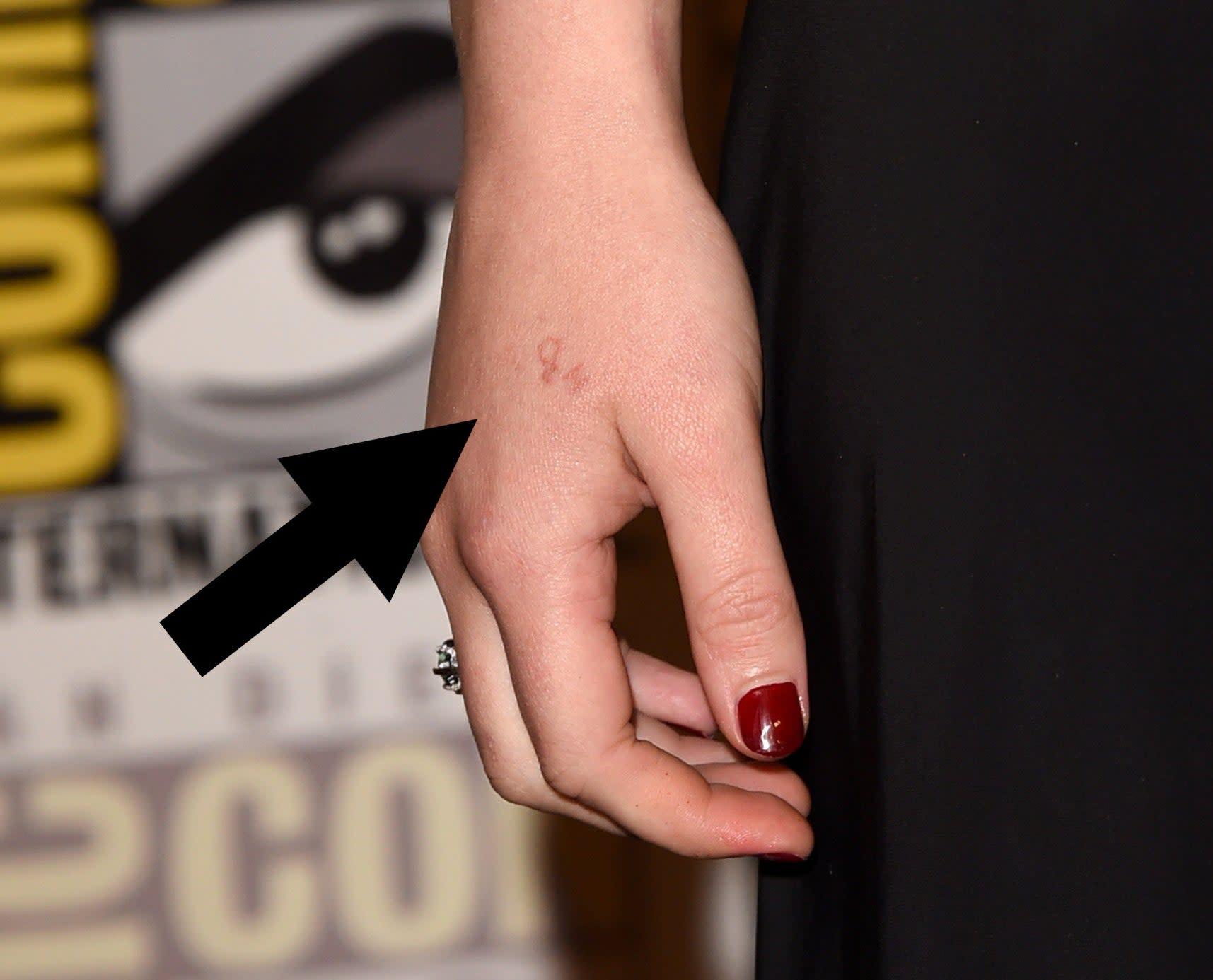 Close-up da mão de Jennifer Lawrence com uma flecha apontando pra tatuagem quase imperceptível