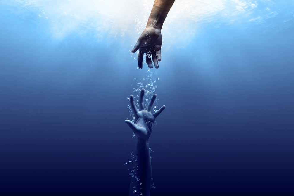 A hand reaching for another hand underwater