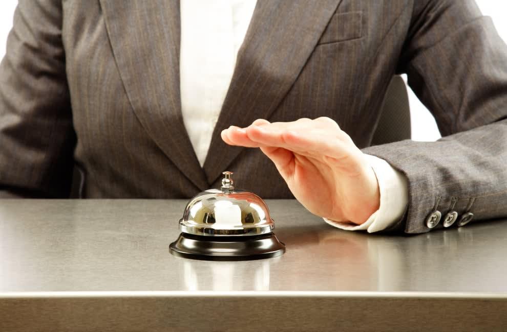 mão apertando campainha de hotel