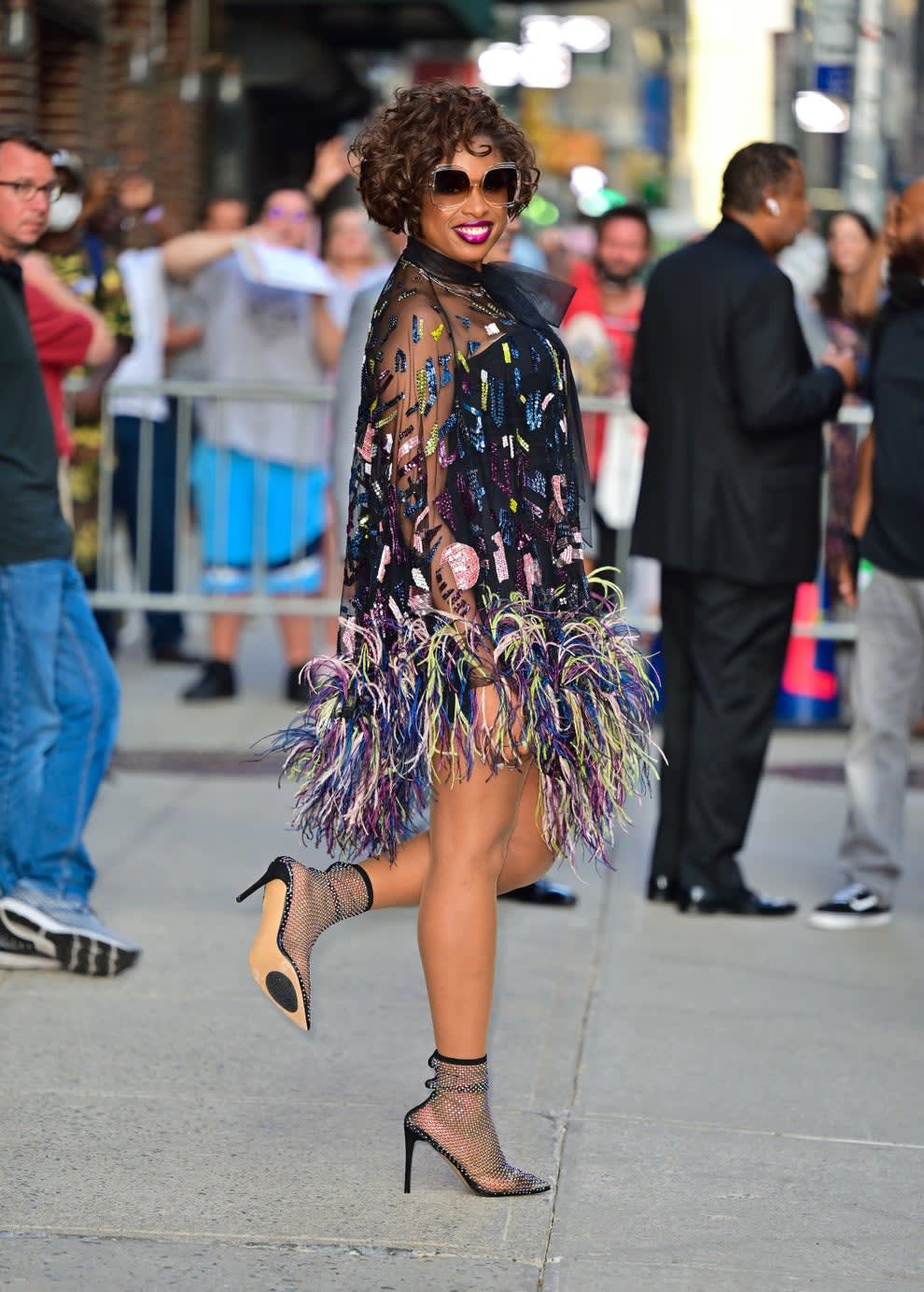 Jennifer wears a multi-colored, mini-dress that's made of mesh on top and feathered on the bottom with a bow around the neck. She also wears fishnet ankle boots.