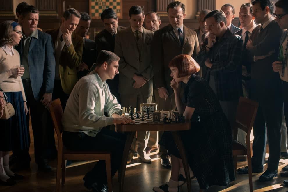 Beth e um oponente jogando uma partida enquanto várias pessoas assistem
