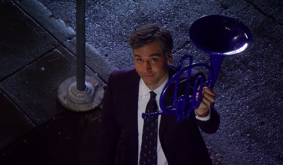 Ted holding up the blue French horn on the sidewalk