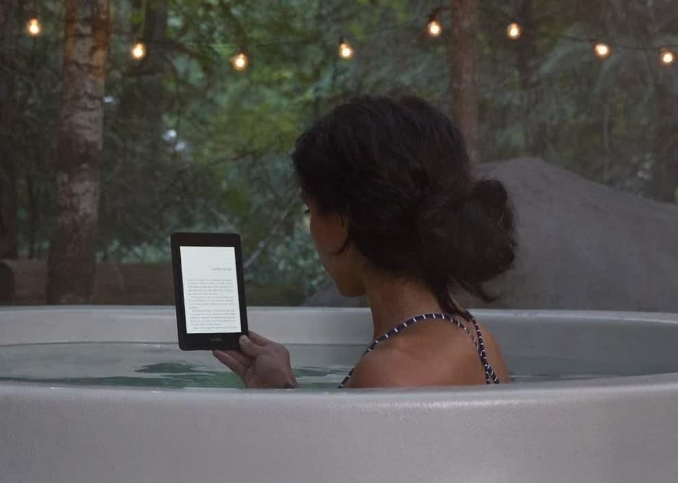 Foto de uma mulher de costas segurando um Kindle dentro de uma banheira de hidromassagem, em uma área externa cercada por árvores e luzes decorativas penduradas.