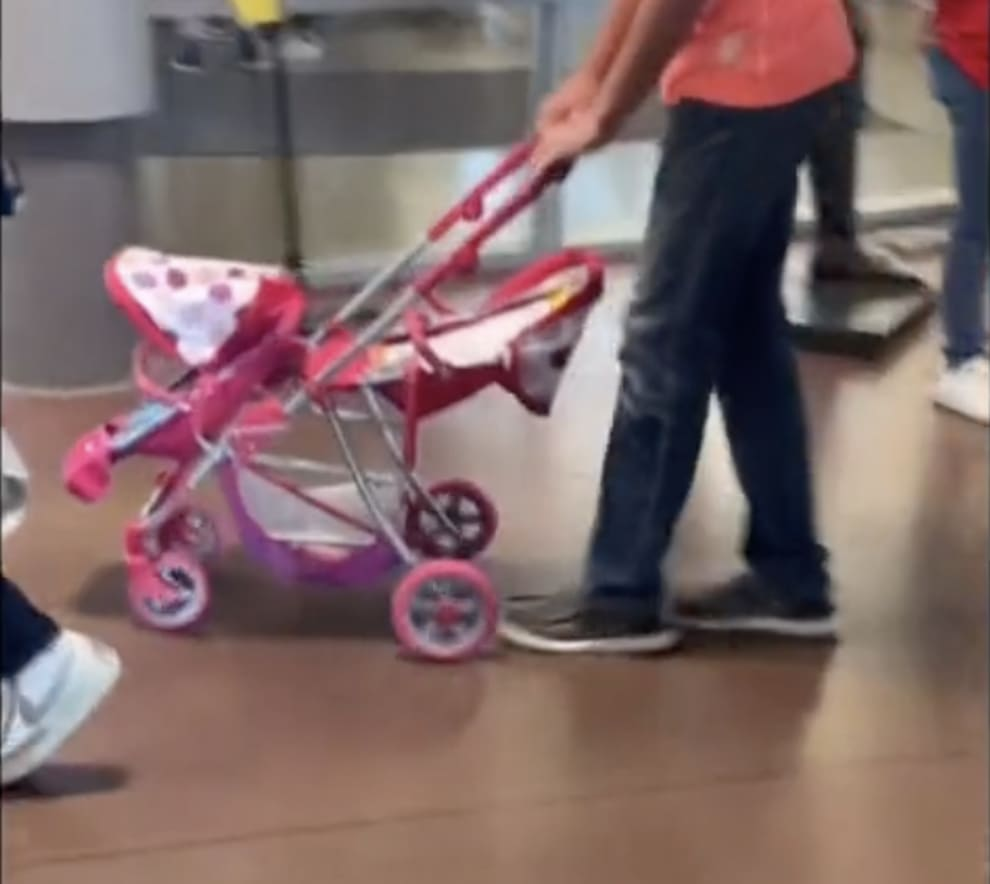 A student pushing a light-colored stroller that can hold two small children