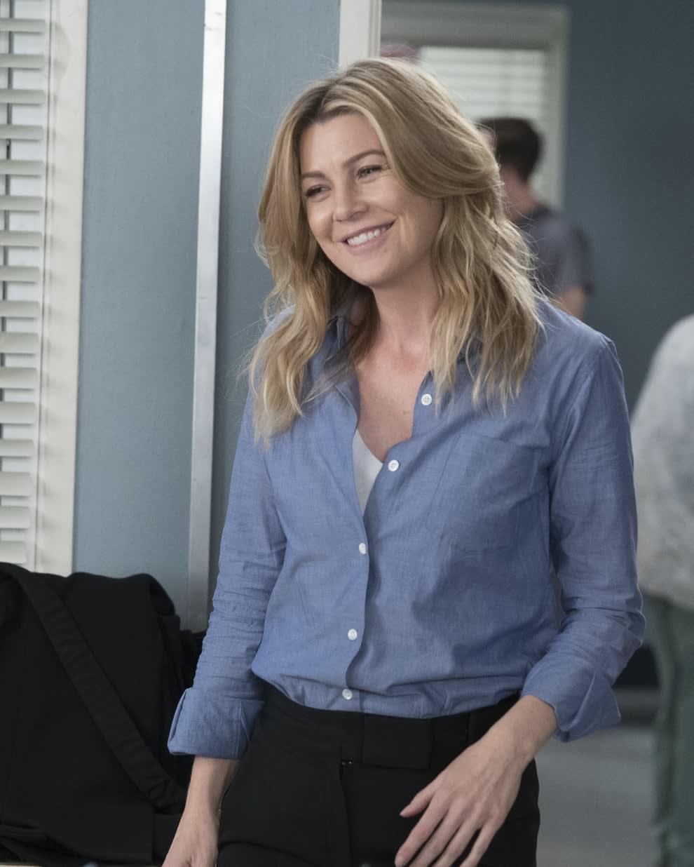 Ellen Pompeo smiles to someone off-camera on Grey's Anatomy