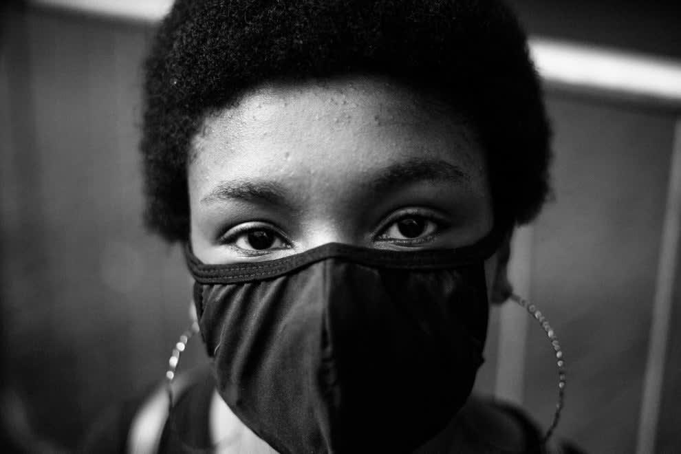 Fotografia em close de jovem negra usando grandes brincos de argola e máscara preta.