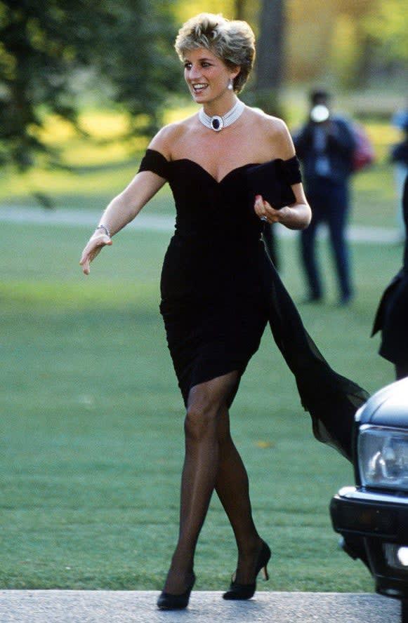Diana usando um vestido preto, sapato de salto alto preto e um grande colar com uma joia preta centralizada.