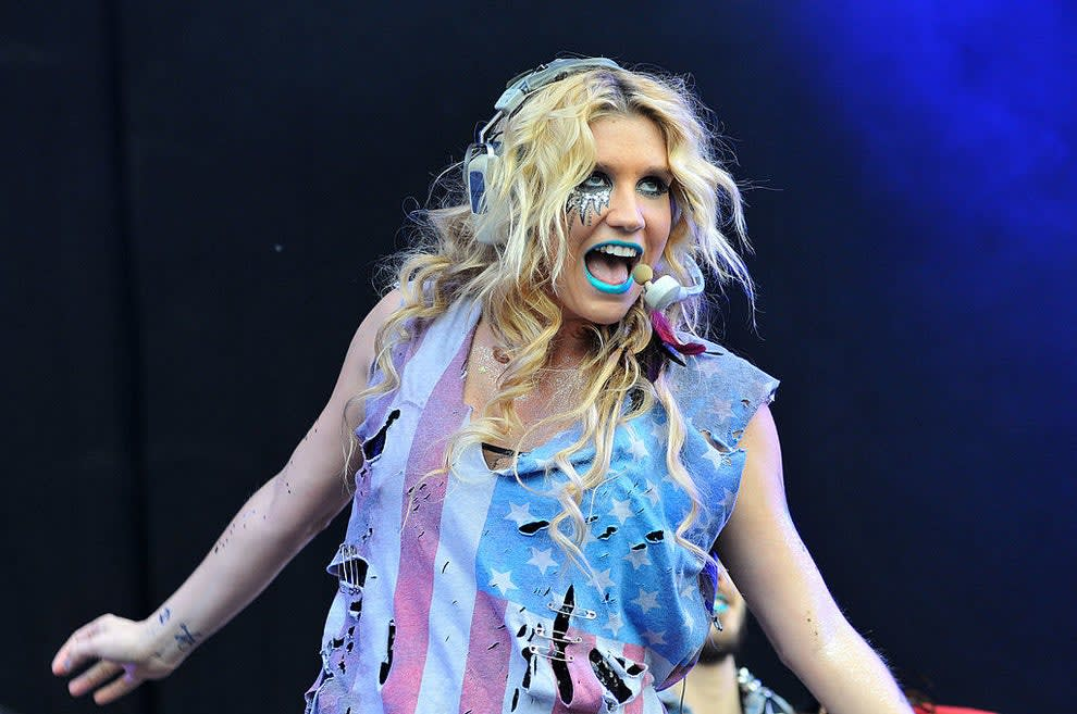 Kesha performing on stage in a torn-up American flag tank top