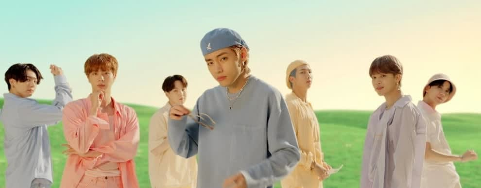 BTS wear different colored clothes and stand in a CG field