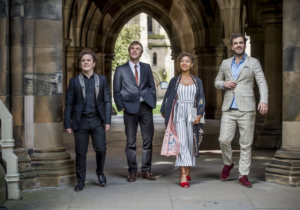 Angus, Dylan, Evie and Luke wear formal clothes and walk through an archway smiling