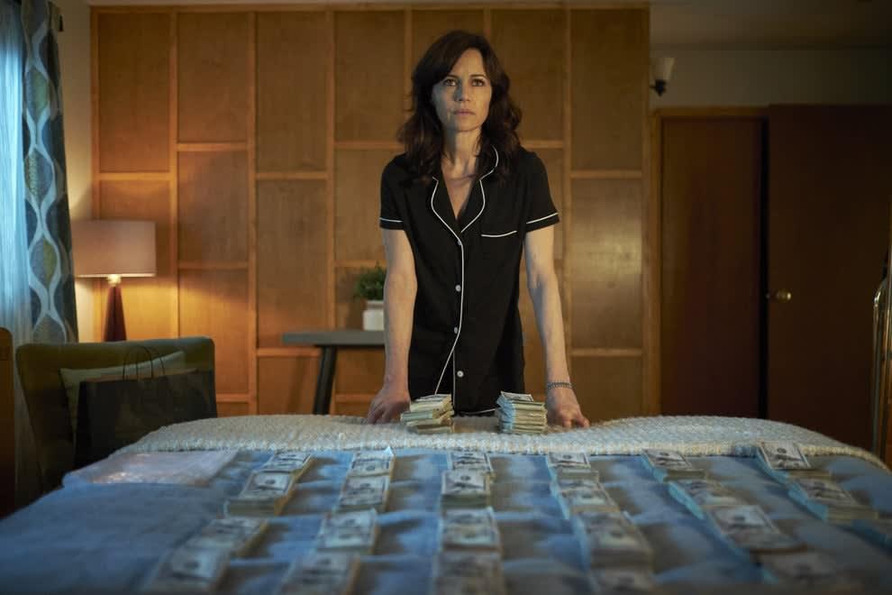 Imagem da atriz Carla Gugino na série Jett. Elas está parada na frente de uma cama onde há várias notas de dólar.