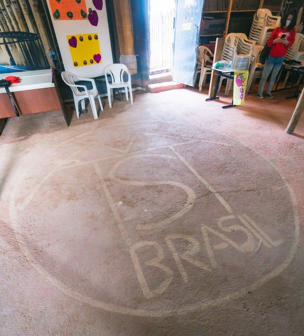 Logotipo do MTST Brasil pintado no chão da área de convivência da ocupação.