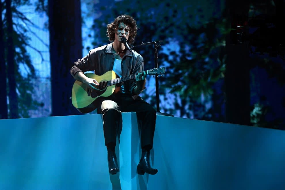 Shawn sits on a ledge on a stage while performing and playing guitar